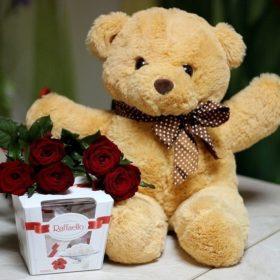 Мішка з букетом троянд і цукерками фото